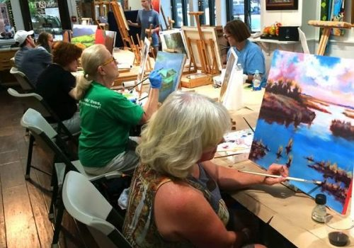 group of people painting canvases