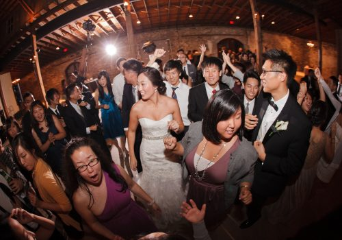 Fish-eye lens picture of people dancing at wedding