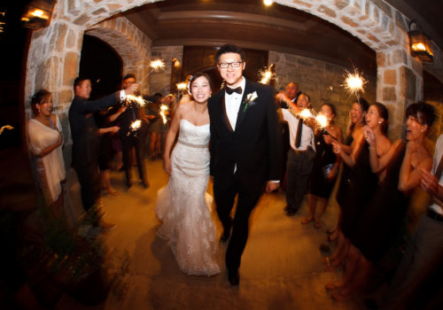 bride and groom leaving wedding through sparklers