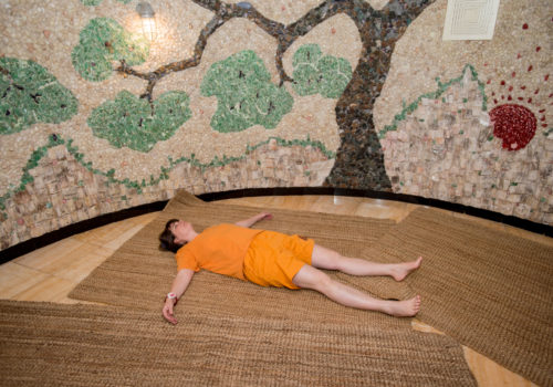 woman laying on mat on the ground