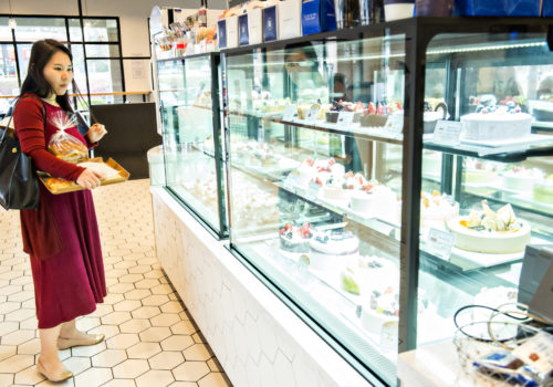 woman looking at case of desserts