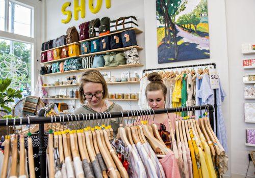 girls browsing clothing rack