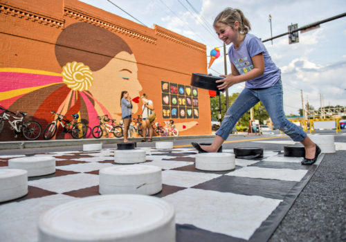 Little girl playing giant checkers
