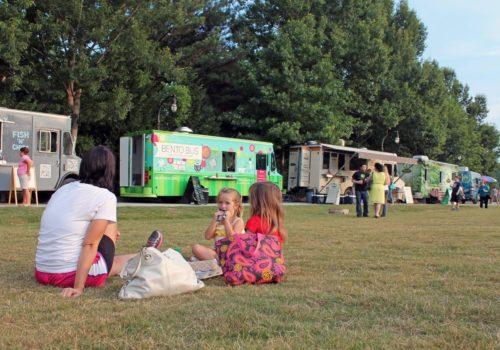 kids sitting on grass eating