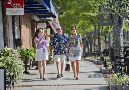 people walking down sidewalk