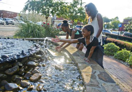 girls playing in fountain