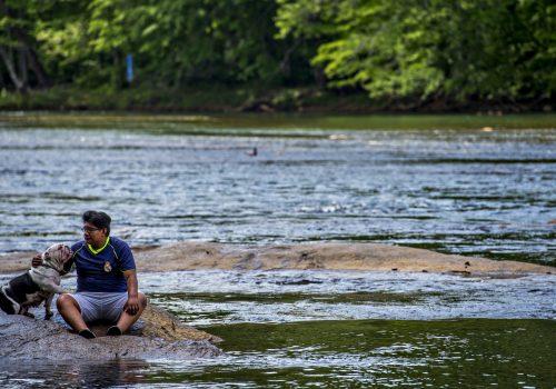 man and dog in lake