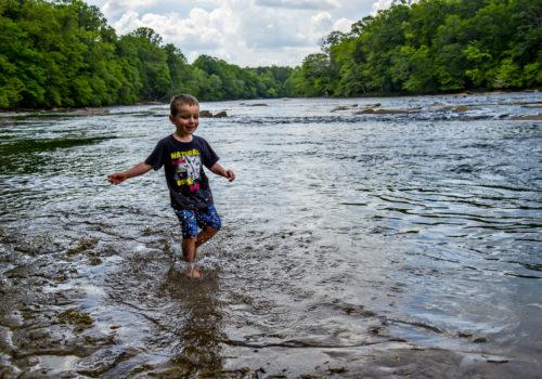 boy wading through lake