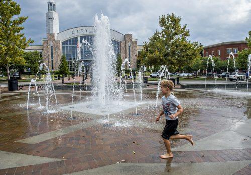 child running around fountain