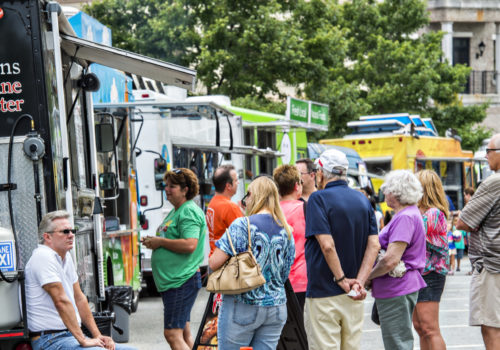 people purchasing food at food trucks