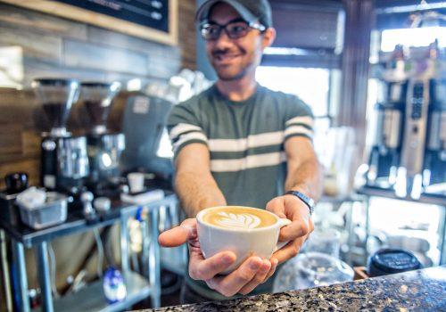 man holding coffee cup at boulder creek coffee