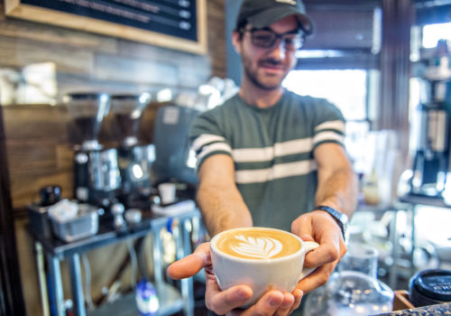 man holding cup of espresso