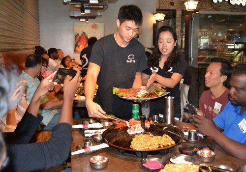 people serving korean bbq