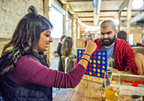 man and woman playing Connect Four