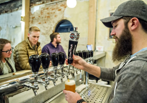 man pouring beer from tap