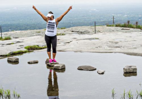 woman raising arms in air