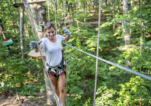 woman walking on safely line through trees