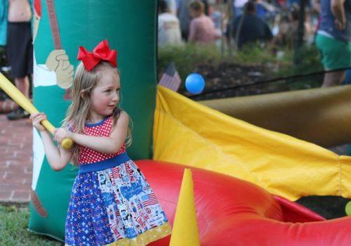 little girl in dress hitting plastic ball with bat