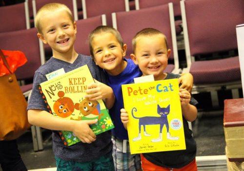 three children smiling, holding books