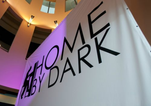 "Black and white banner reading ""Home by Dark"""