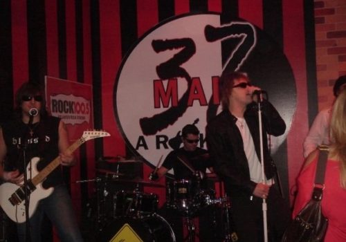 signer, guitarist and drummer performing