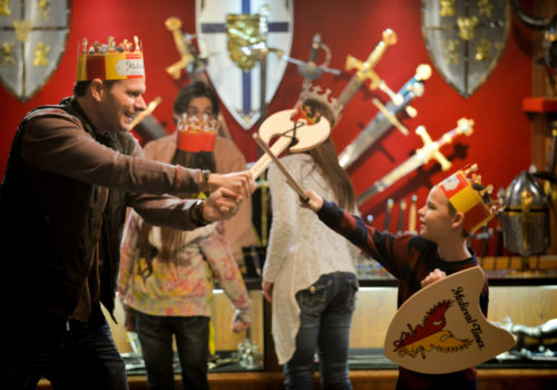 Man and boy play sword fighting at Medieval Times