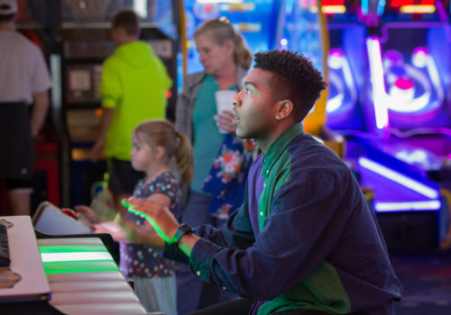 young man playing arcade game