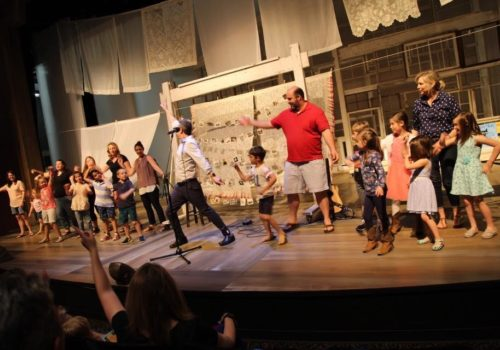 adults and children on stage
