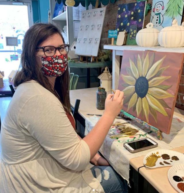 Eye Candy Art Studio woman painting a canvas