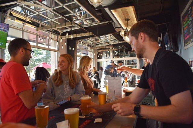 bartender serving woman beer at StillFire Brewing